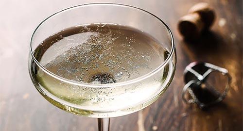 Prosecco i ett coupéglas på ett träbord tillsammans med en kork och grimma från flaska.